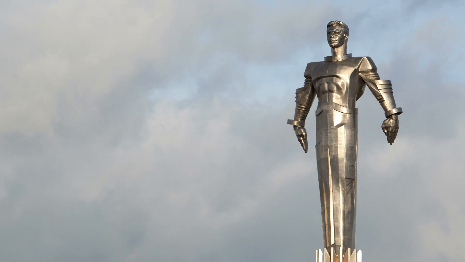 Time lapse of clouds running behind monument to Yuri Gagarin. Metal statue  of famous Russian cosmonaut in Moscow. Wide shot.