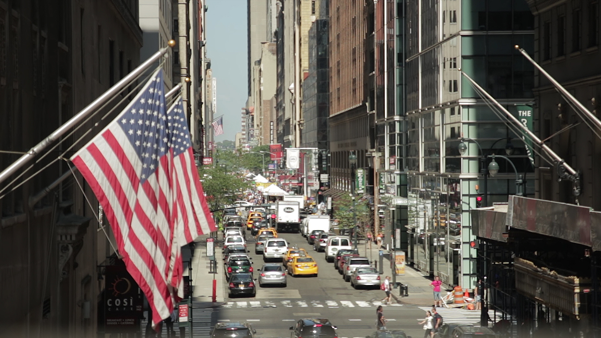 New York City street with US flag in foreground and traffic in background