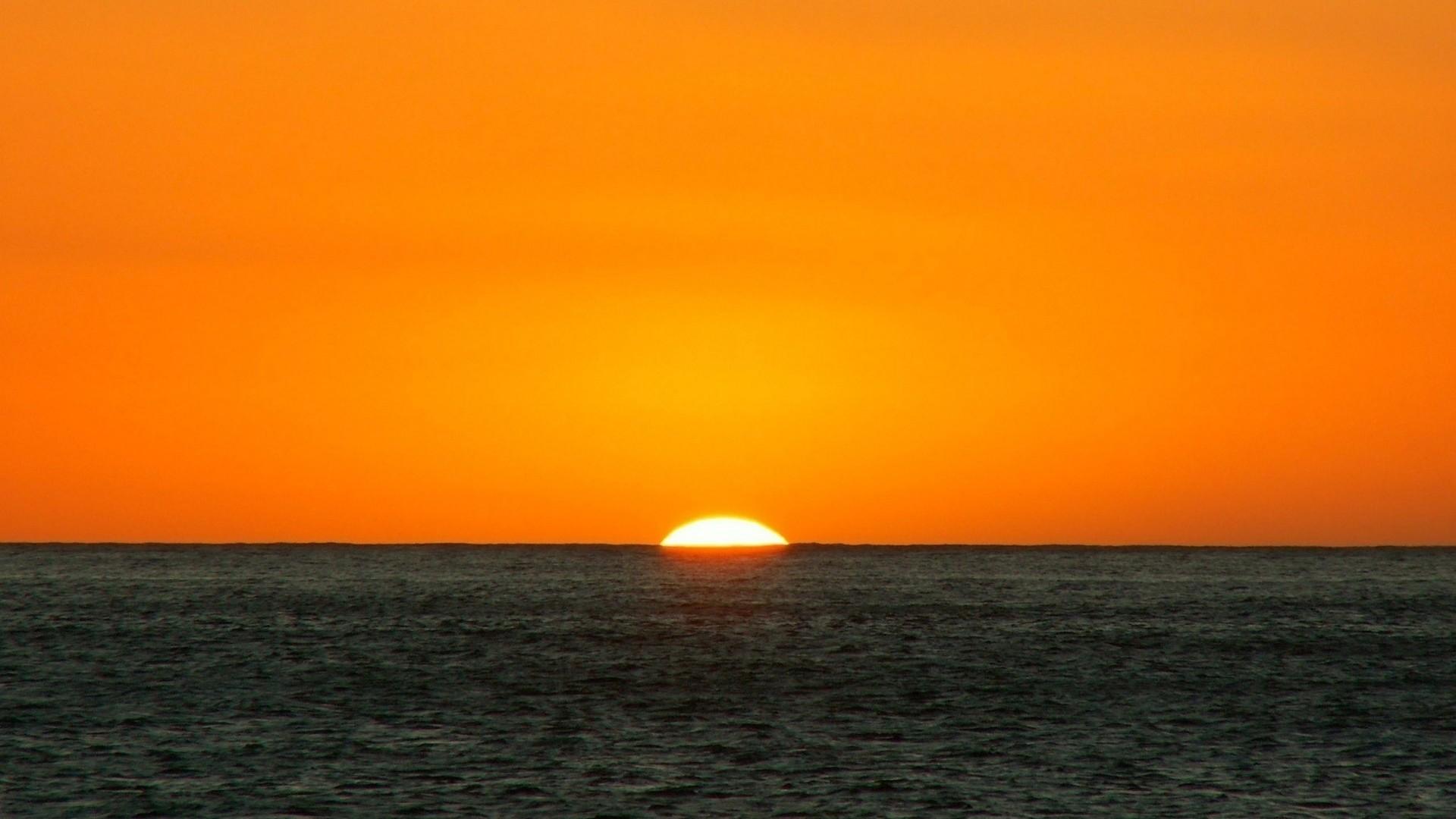 Preview wallpaper orange, dark blue, sea, horizon, sun 1920×1080