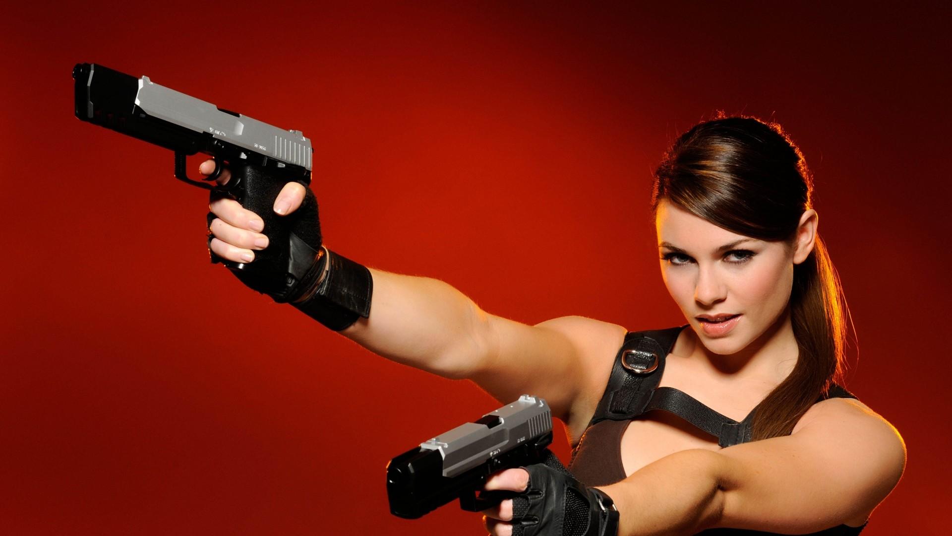 Preview wallpaper girl, guns, red background, blonde, blue eyes, hands  1920×1080