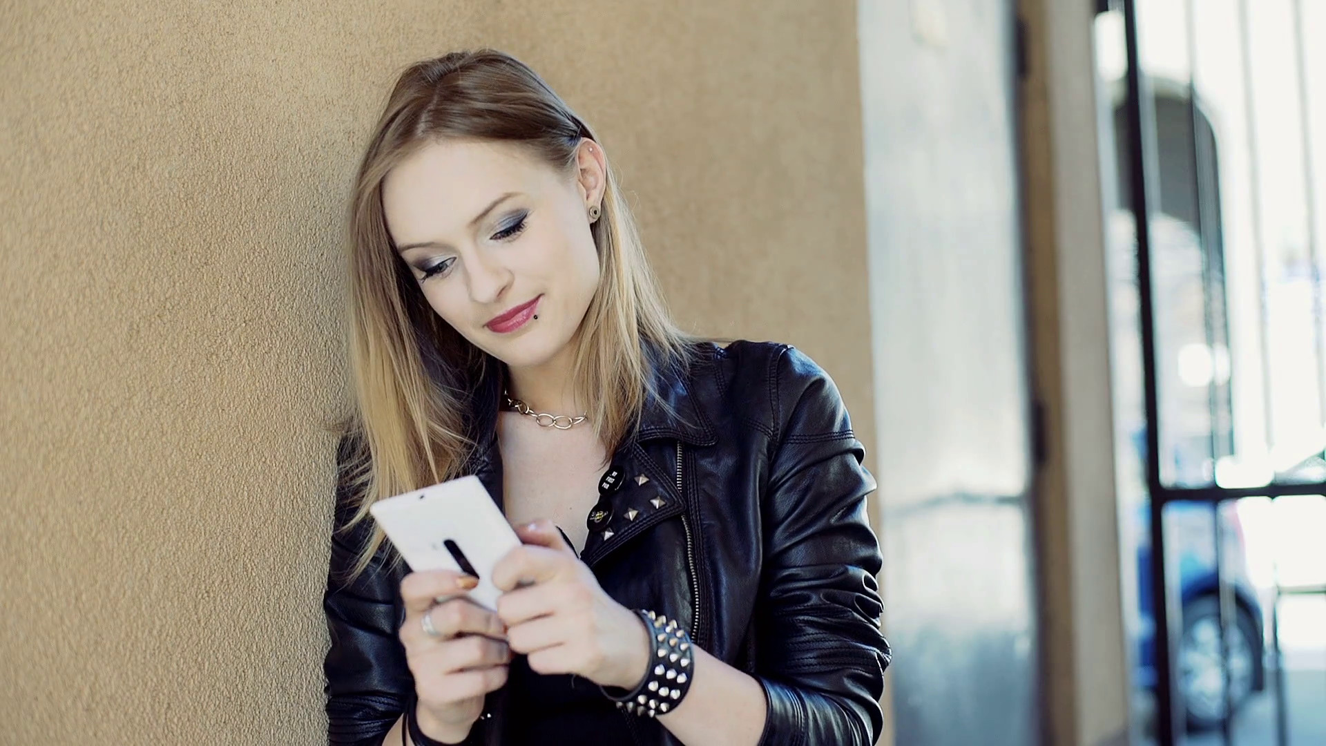 Punk girl texting on smartphone while leaning on the wall Stock Video  Footage – VideoBlocks
