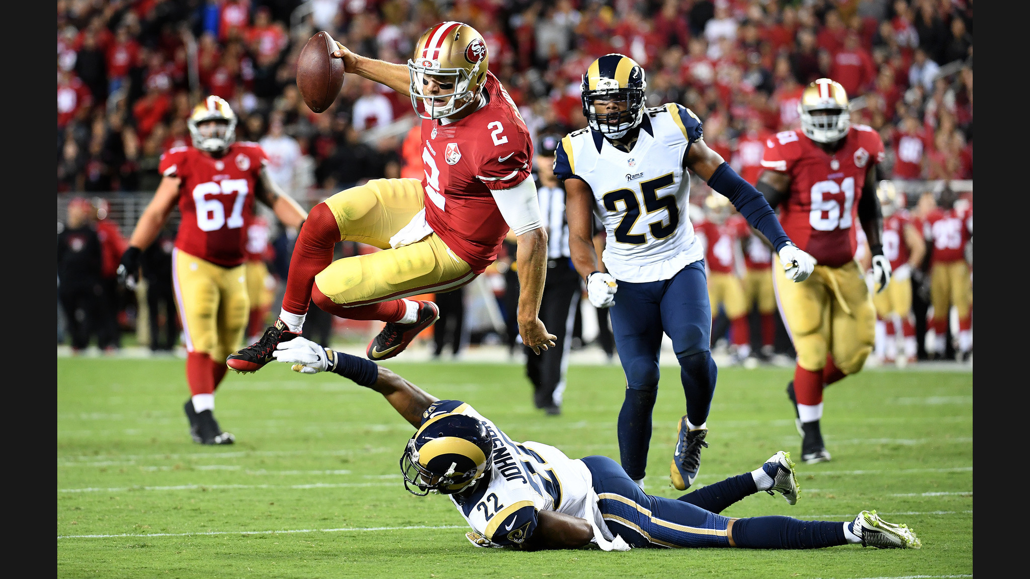 49ers quarterback Blaine Gabbert leaps for a 1st down over Rams cornerback  Trumaine Johnson in the
