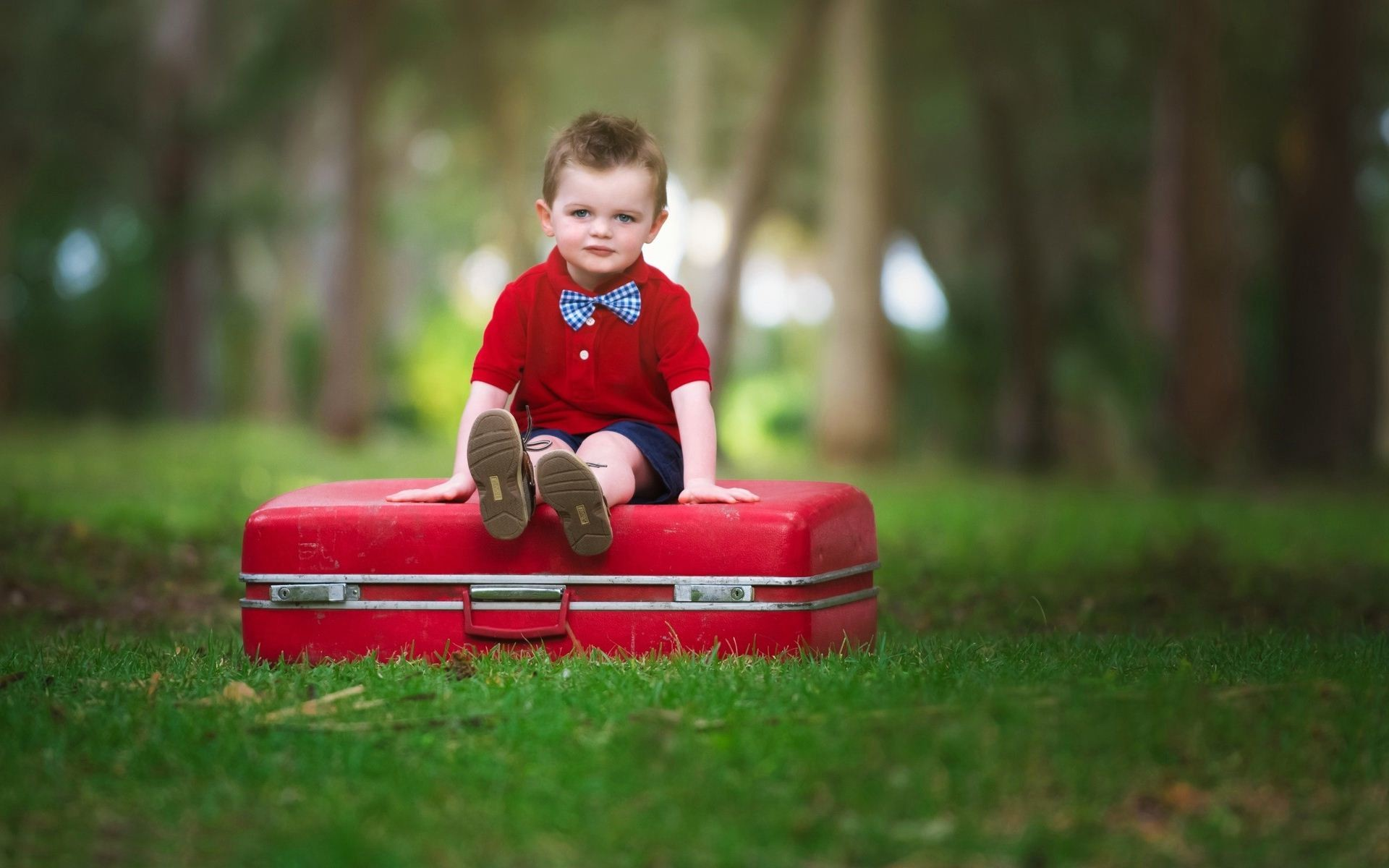 Cute Baby Boy Sitting On Suitcase Wallpaper