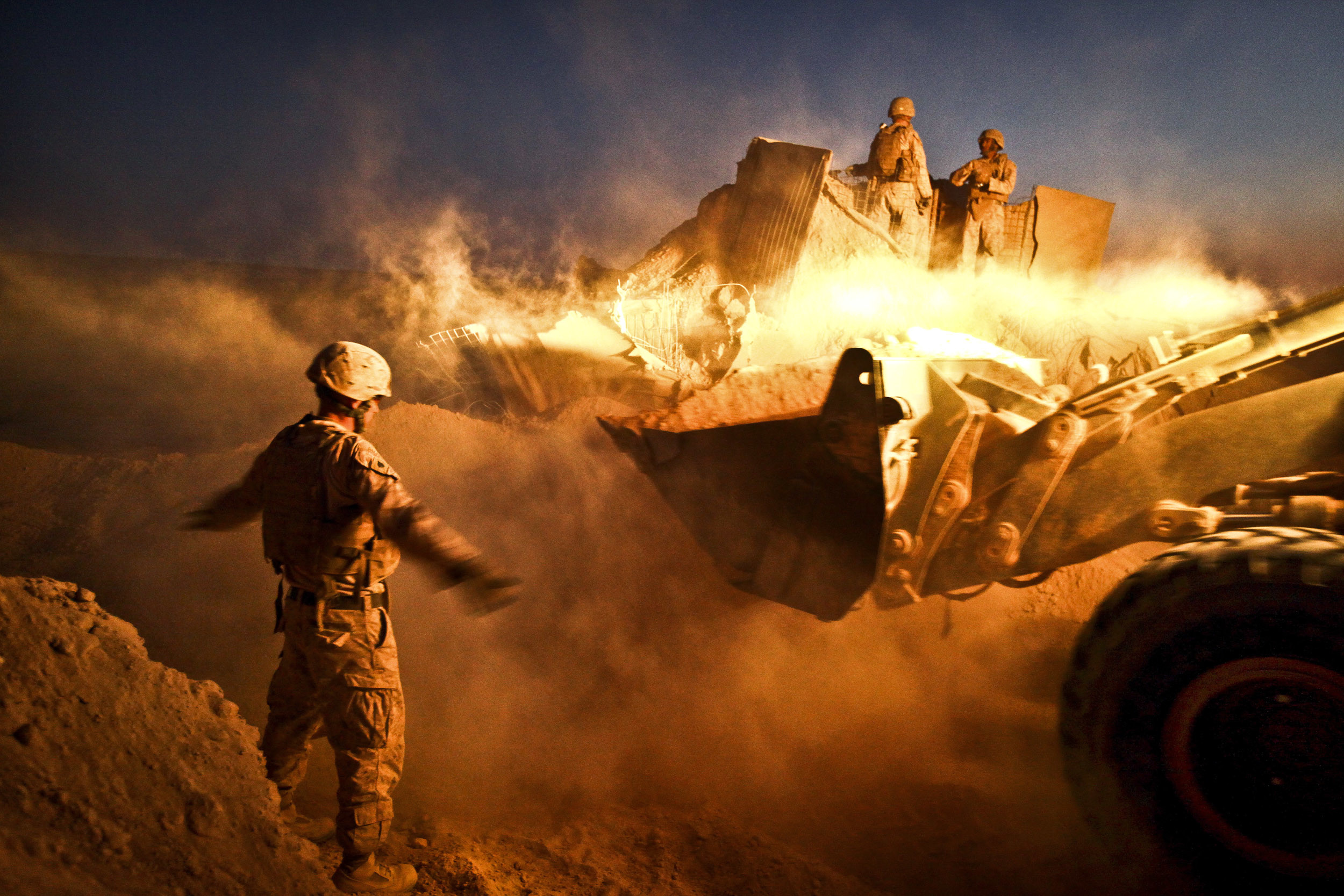 U.S. Marine Corps Sgt. Cody Palfreyman guides a bulldozer as it moves the  berm surrounding
