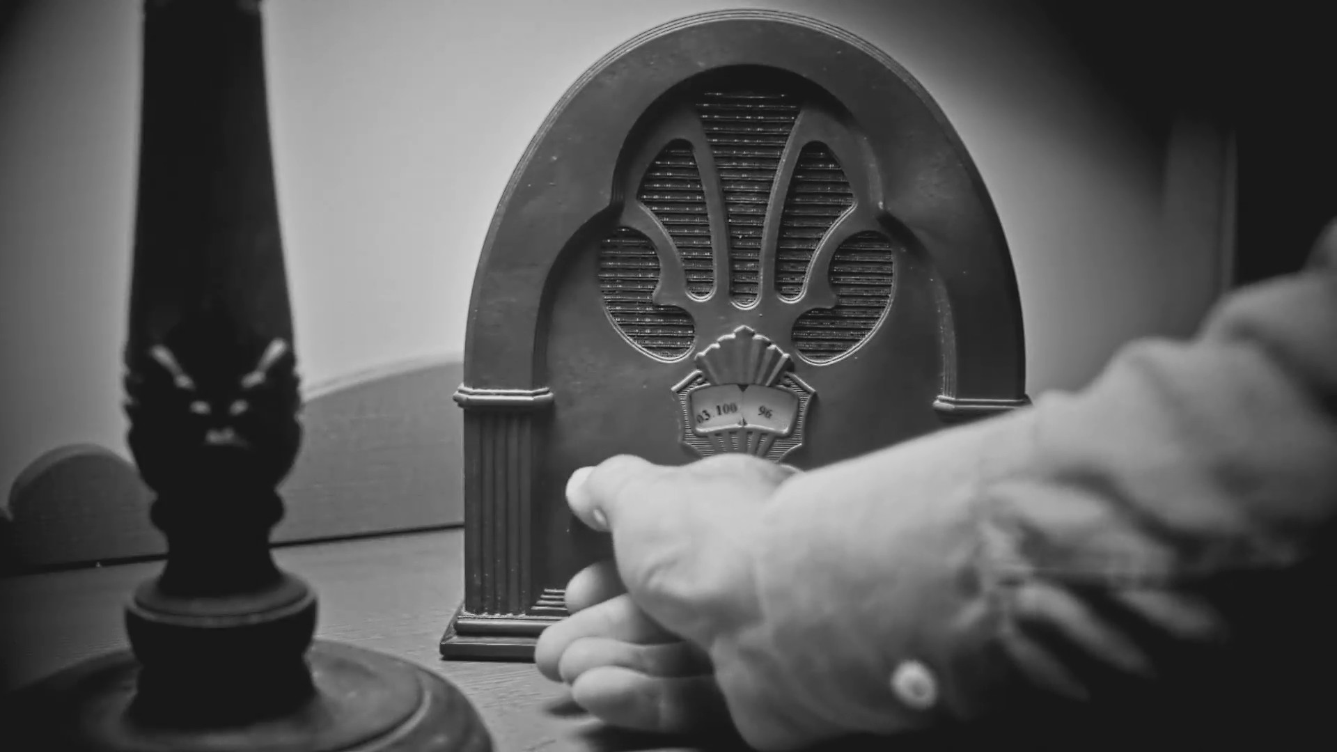 Radio noir film tuning bedroom hand. The hand of a man turns the dial on an  old vintage 1940's radio sitting on a night stand in a bedroom.