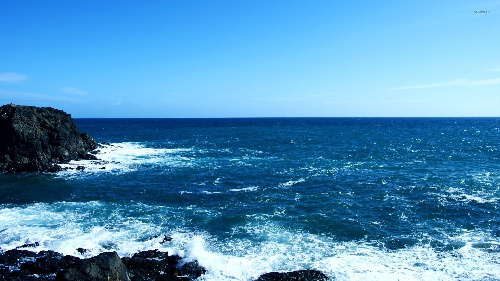 Rocks rising from the blue ocean wallpaper