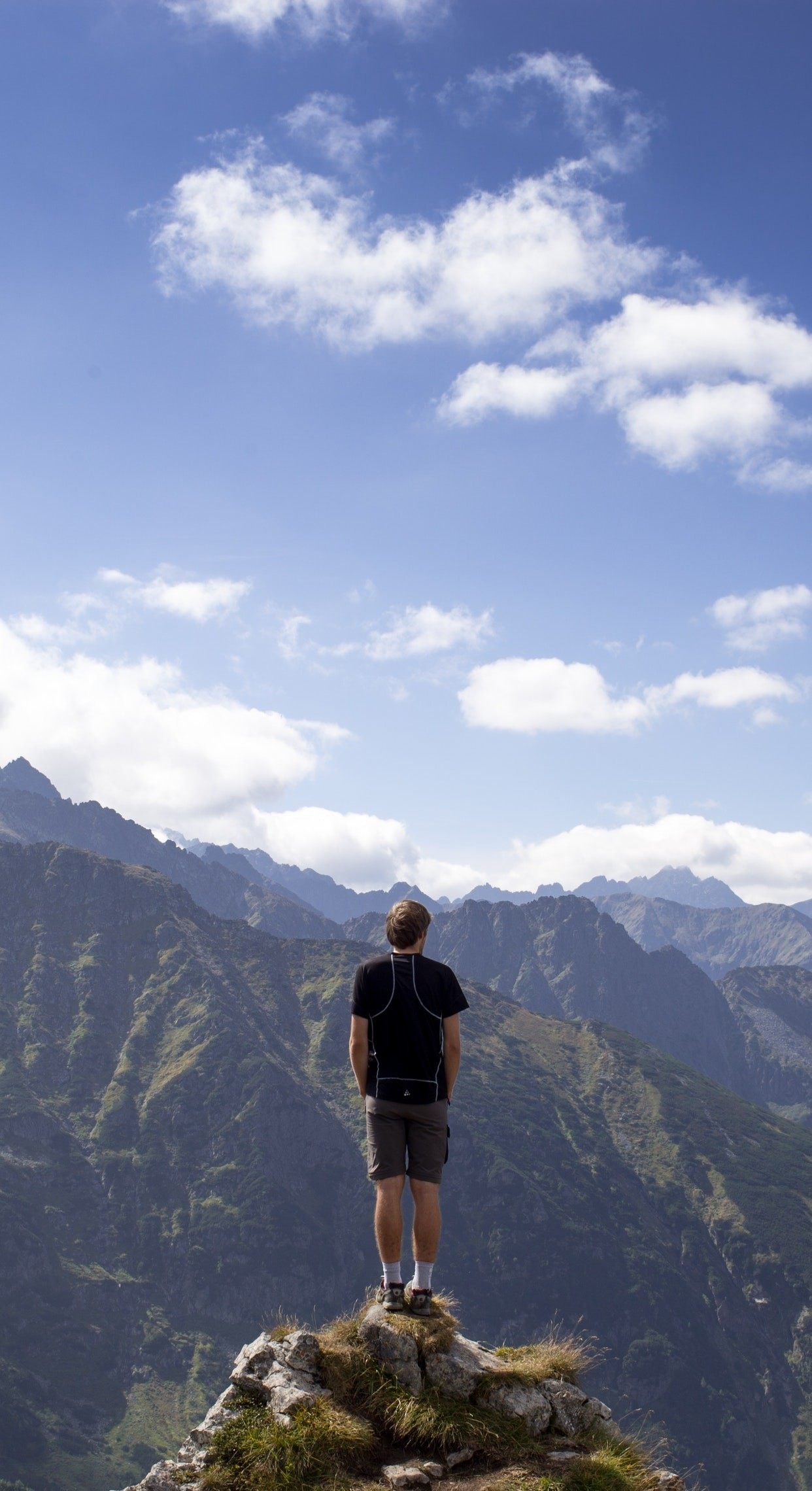 man in black shirt and gray shorts standing on cliff under white and blue cloudy  sky iPhone 7 wallpaper