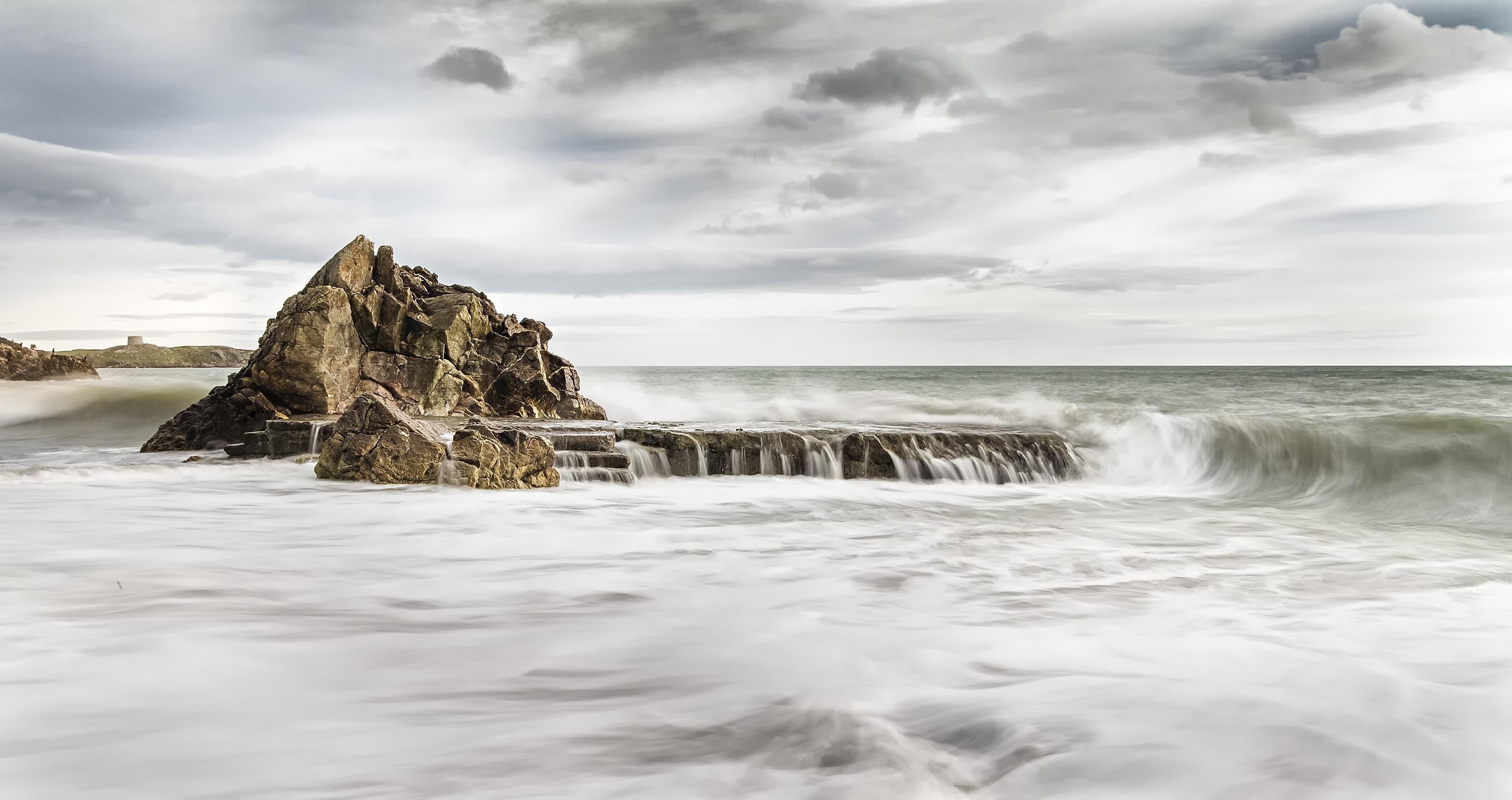 sea waves splashing on grey rock with grey cloudy sky preview