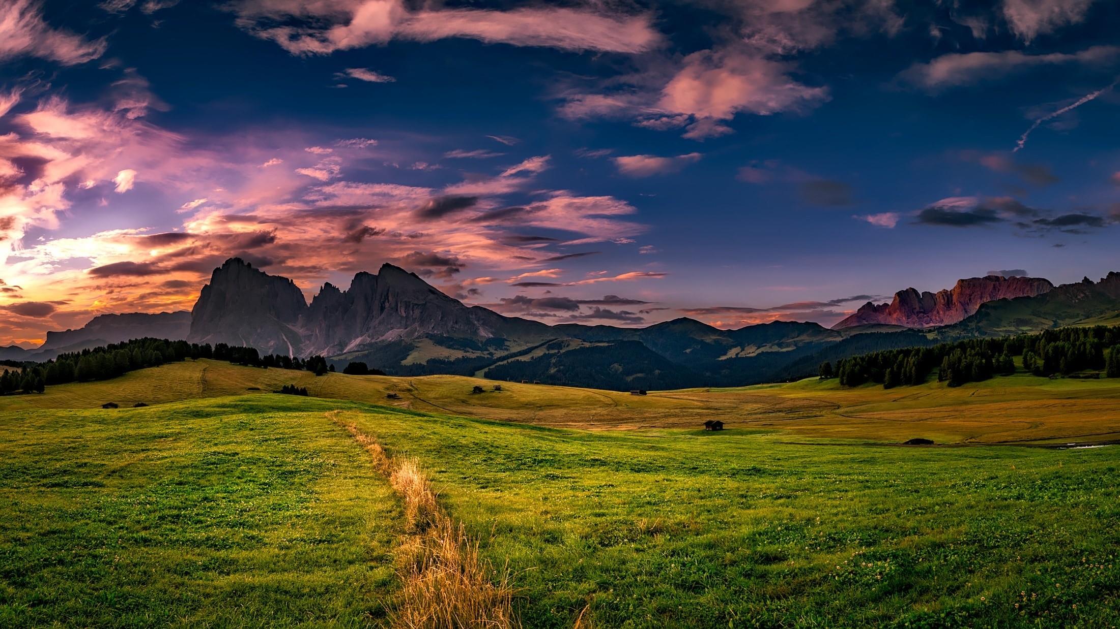 green open field behind hills under dark sky preview