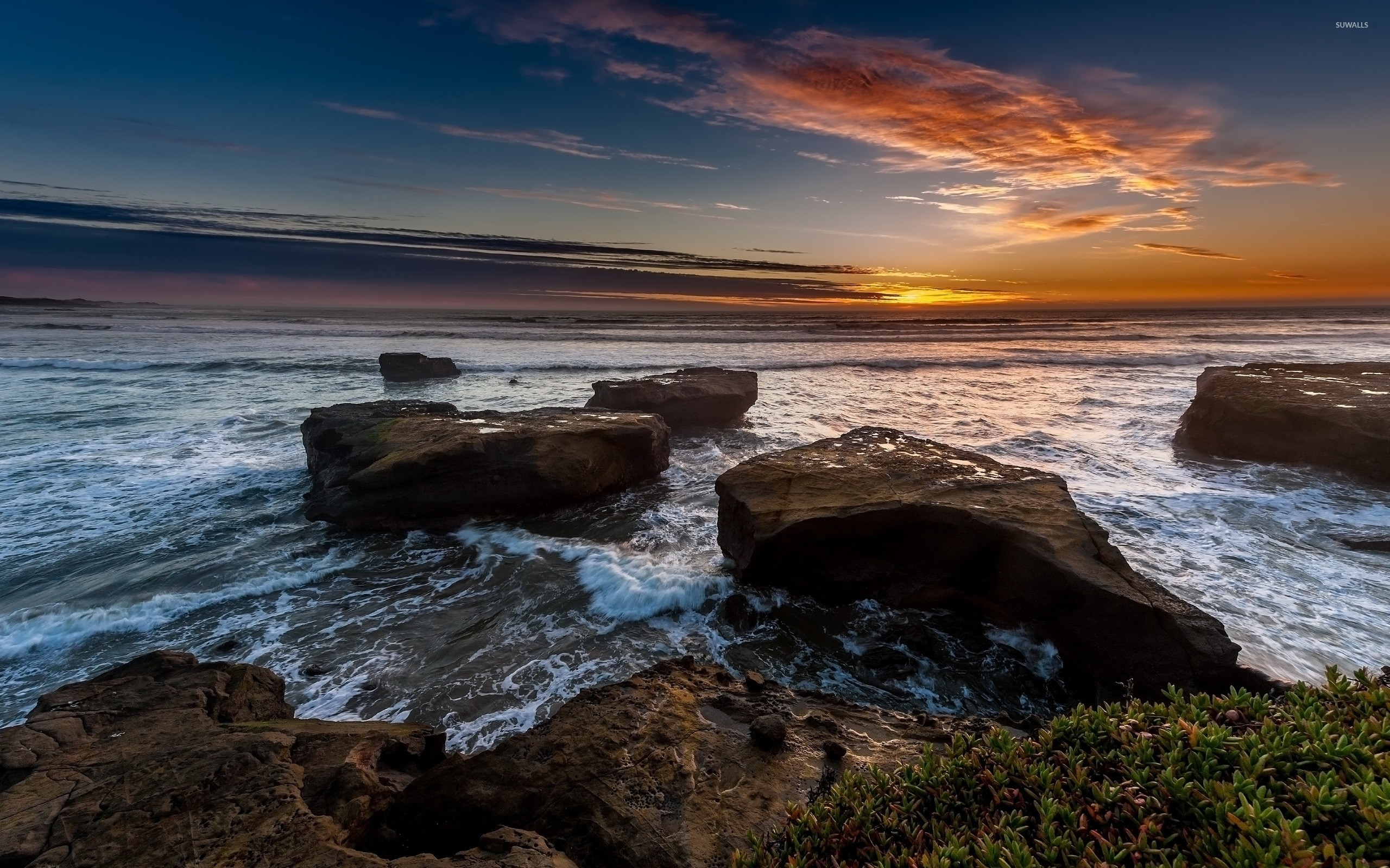 Beautiful ocean sunset above the rocky shore wallpaper