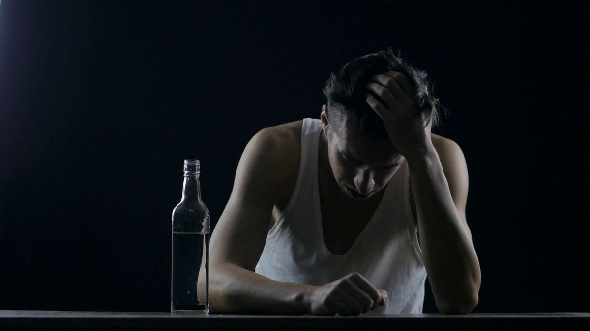 depressed man drinking alcohol alone in a dark room. man in ...