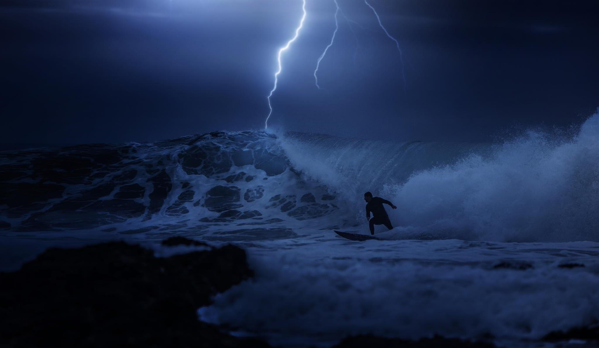 night ocean surfing guy the storm lightning
