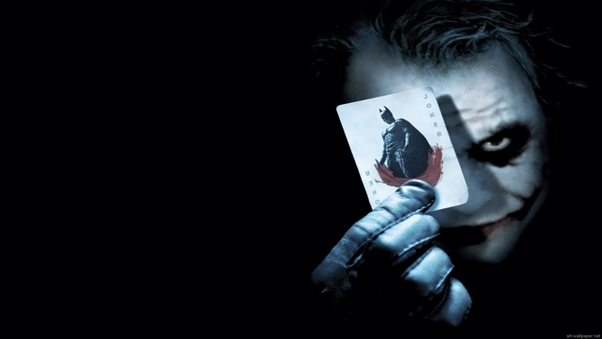 This poster if for the Batman the Dark Knight move. The jokers face and the  playing card he is holding are light colored over a dark background.