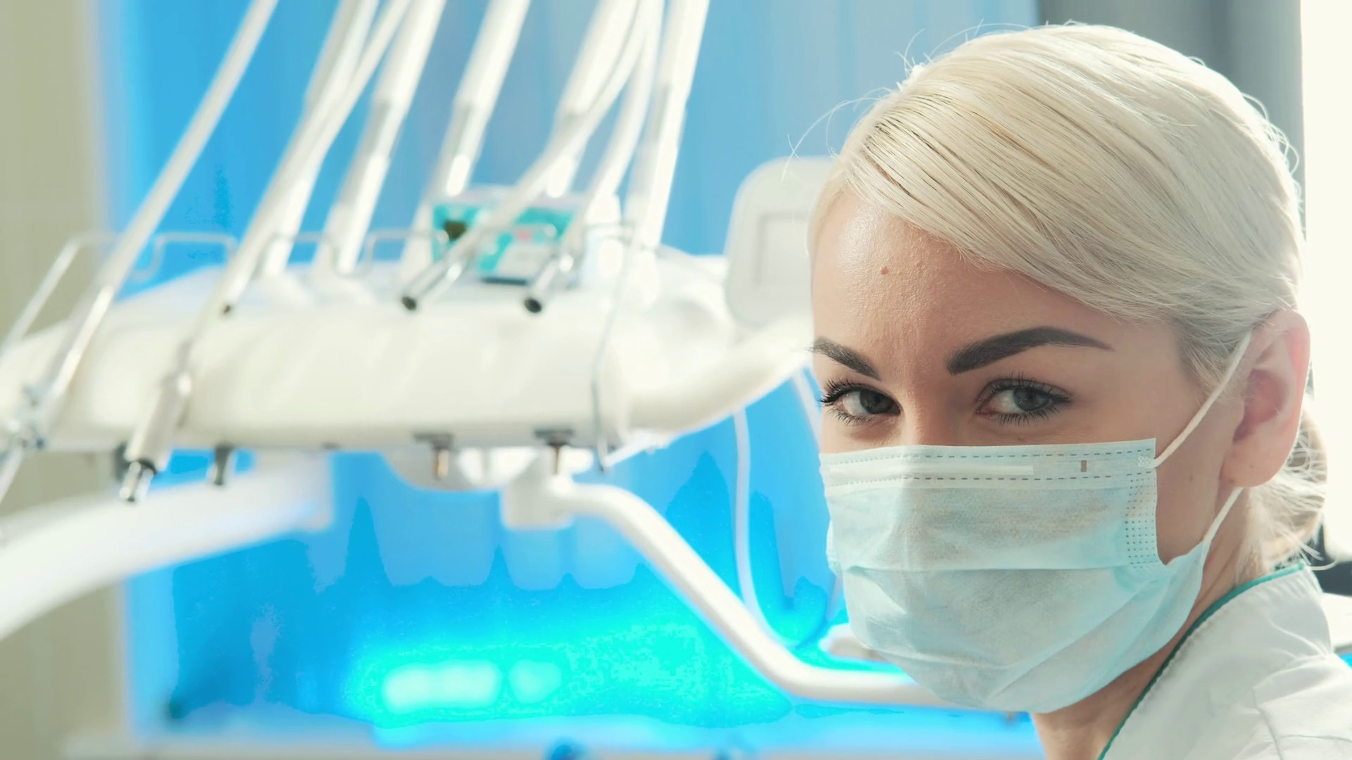 Closeup face of young woman dentist in mask on her in dental office. Video  portrait of beautiful doctor or nurse. beautiful woman with blond braided  hair in …
