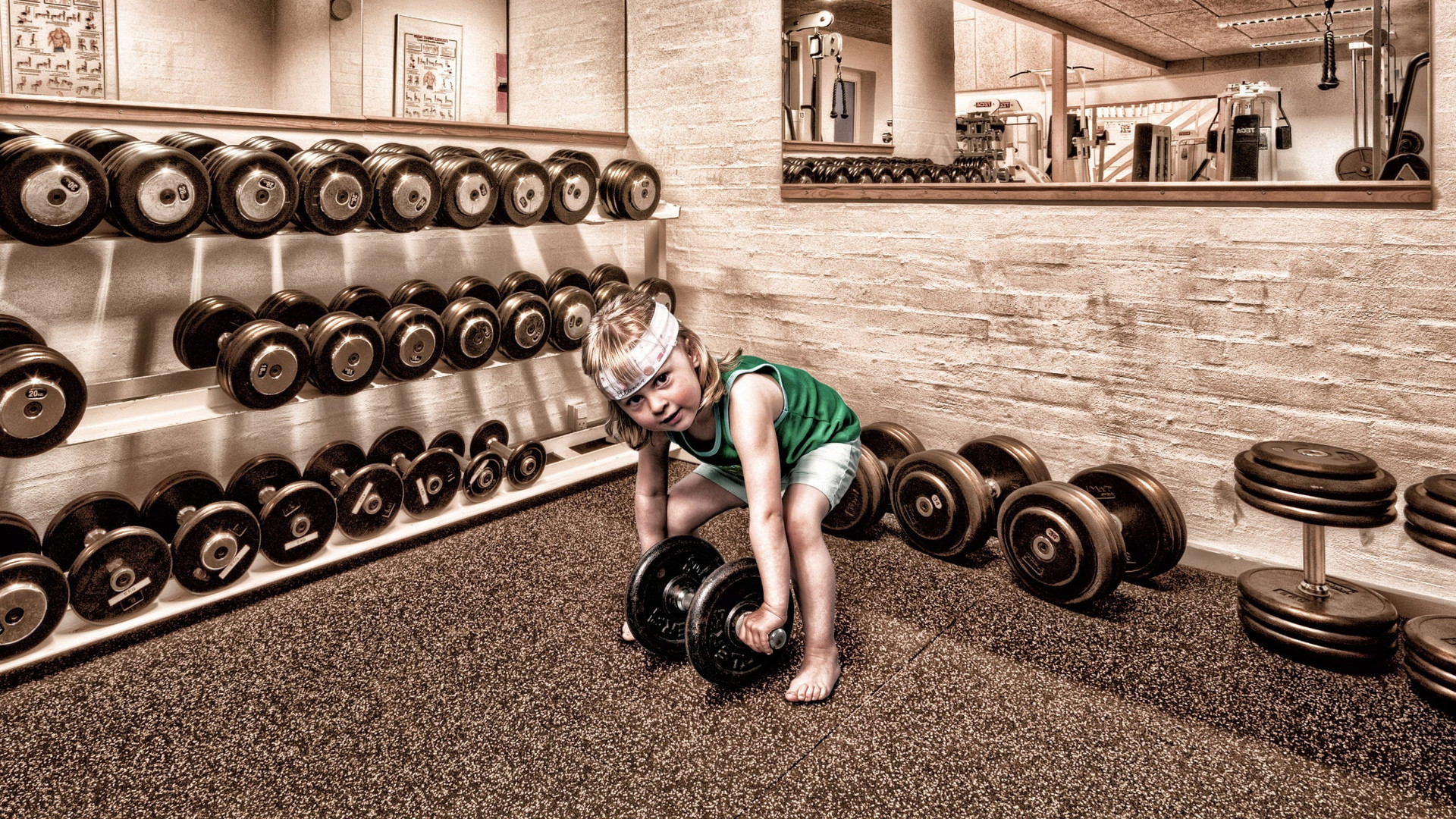 Kid with dumbbells in the gym: