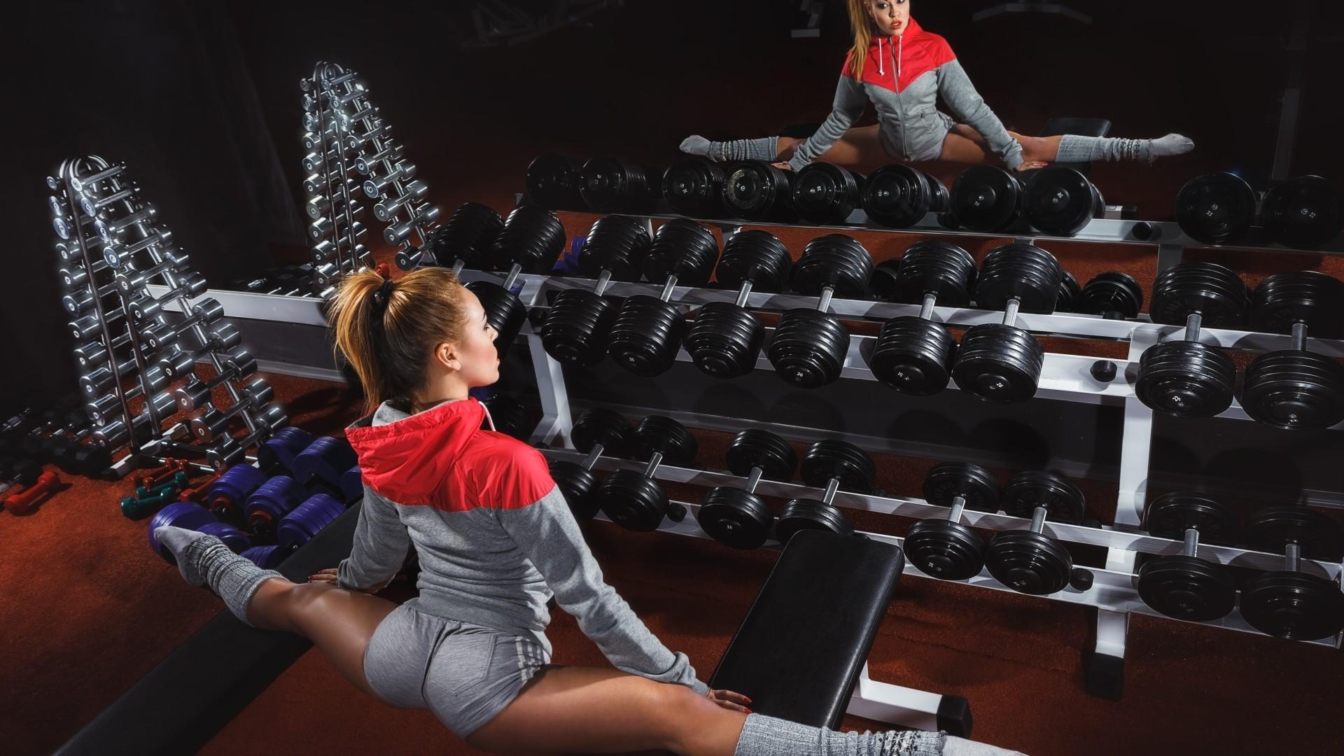 Brunette doing splits in gym: