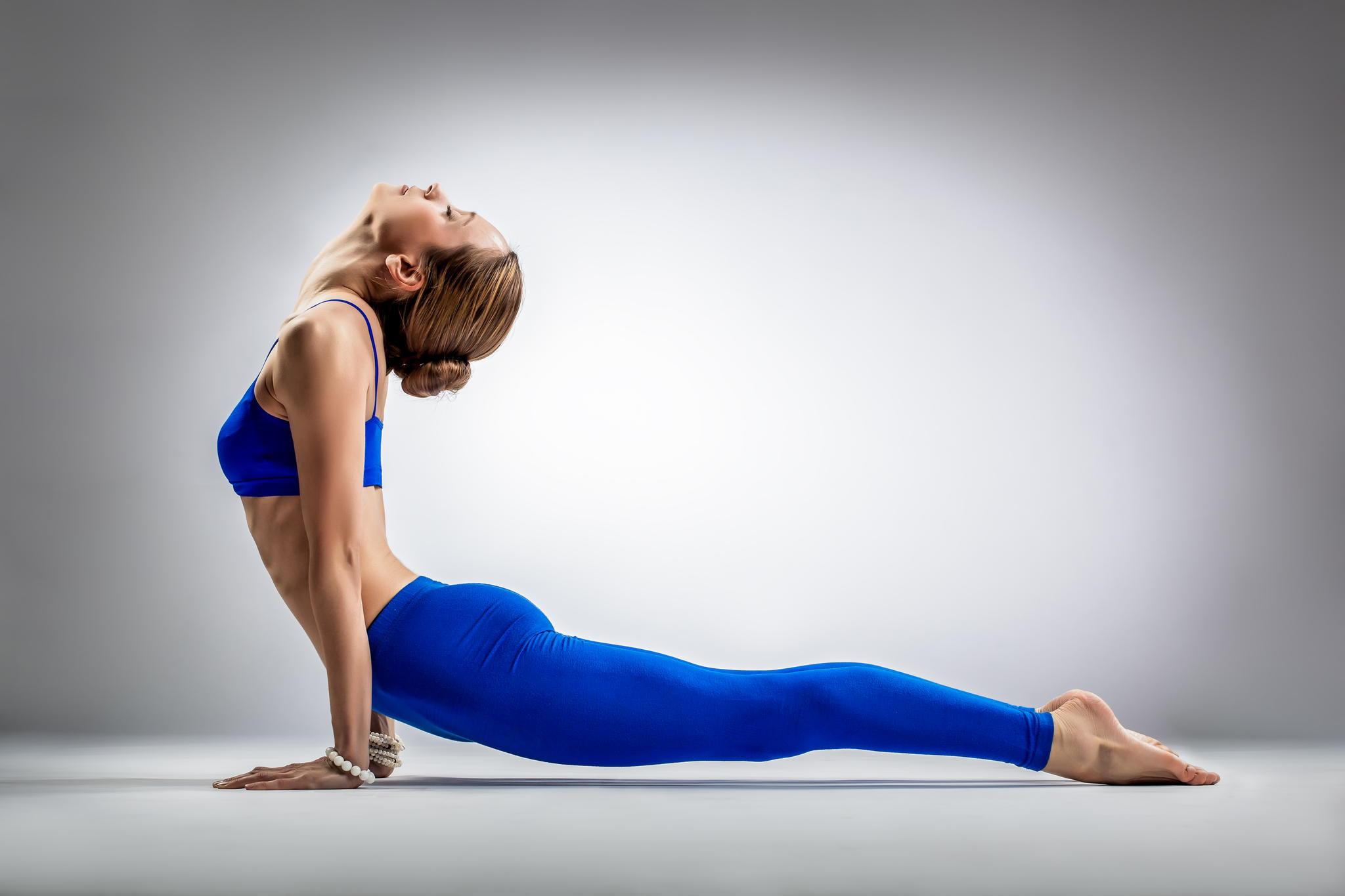 the yoga woman – young beautiful yoga posing on a gray studio background