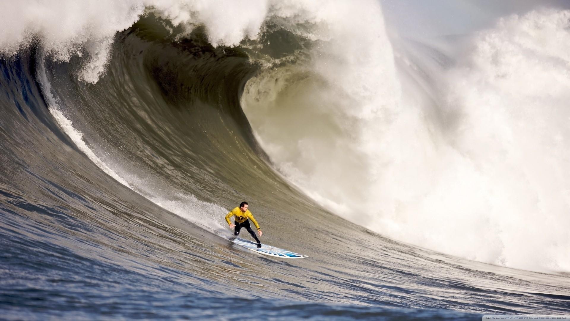 a surfer down a big wave wallpaper