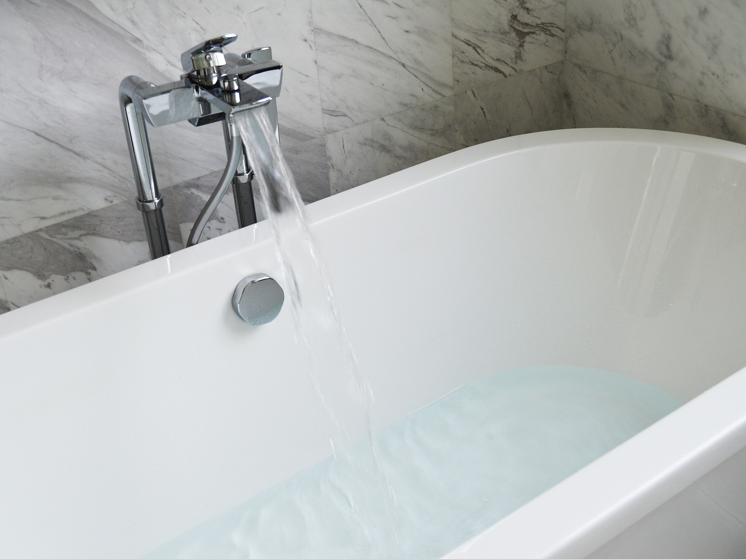 white porcelain oval bath tub and stainless steel faucet